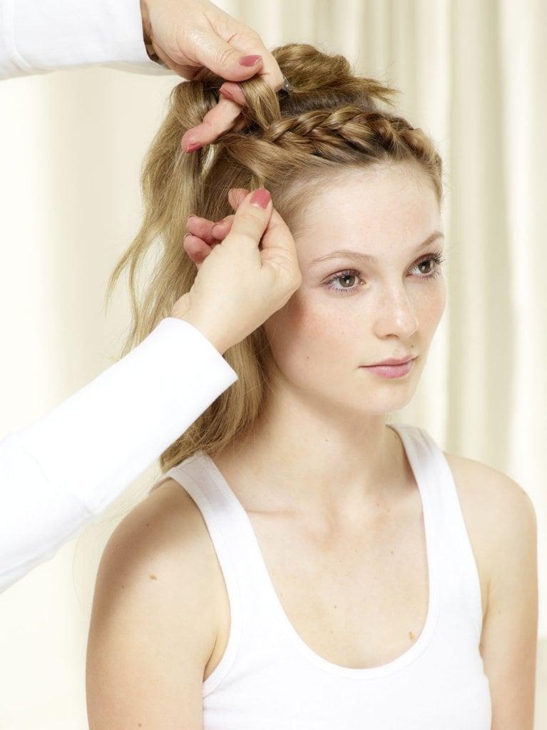 Danach äußere Haarpartien als jeweils mitleren Flechtstrang hineinziehen. Flechtvorgang um den ganzen Kopf bis zum Ausgangspunkt fortsetzen.