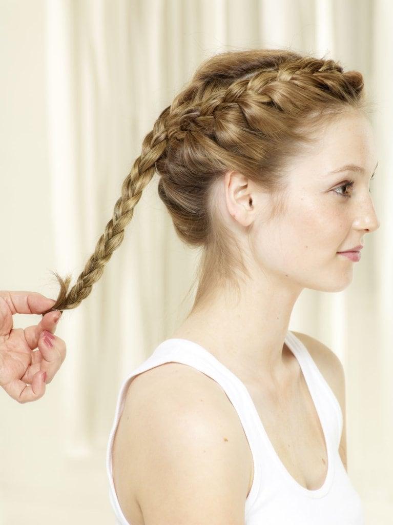 Mittlere Haarsträhne lösen und zu einem klassischen 3er Zopf flechten. Zopf um den Kopf wickeln und mit Haarnadeln befestigen. Am Schluss Flechtfrisur am Haaransatz etwas lockern, um den Style natürlicher wirken zu lassen.