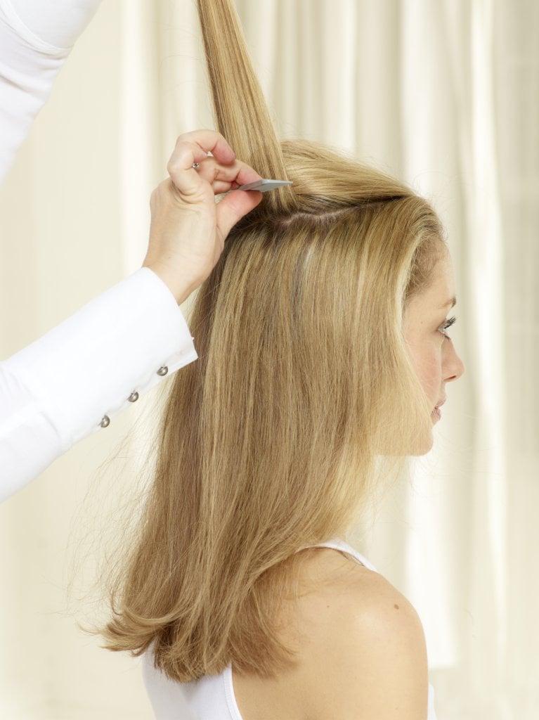 Mit volumengebenden Produkten Fülle ins Haar bringen. Haaransatz toupieren