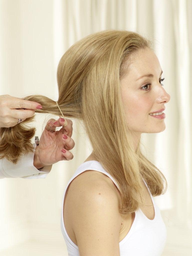 Haar in 3 Strähnen unterteilen, wobei die mittlere Strähne kräftiger sein muss. Mittlere Strähne locker mit einem Haarband zusammenbinden.