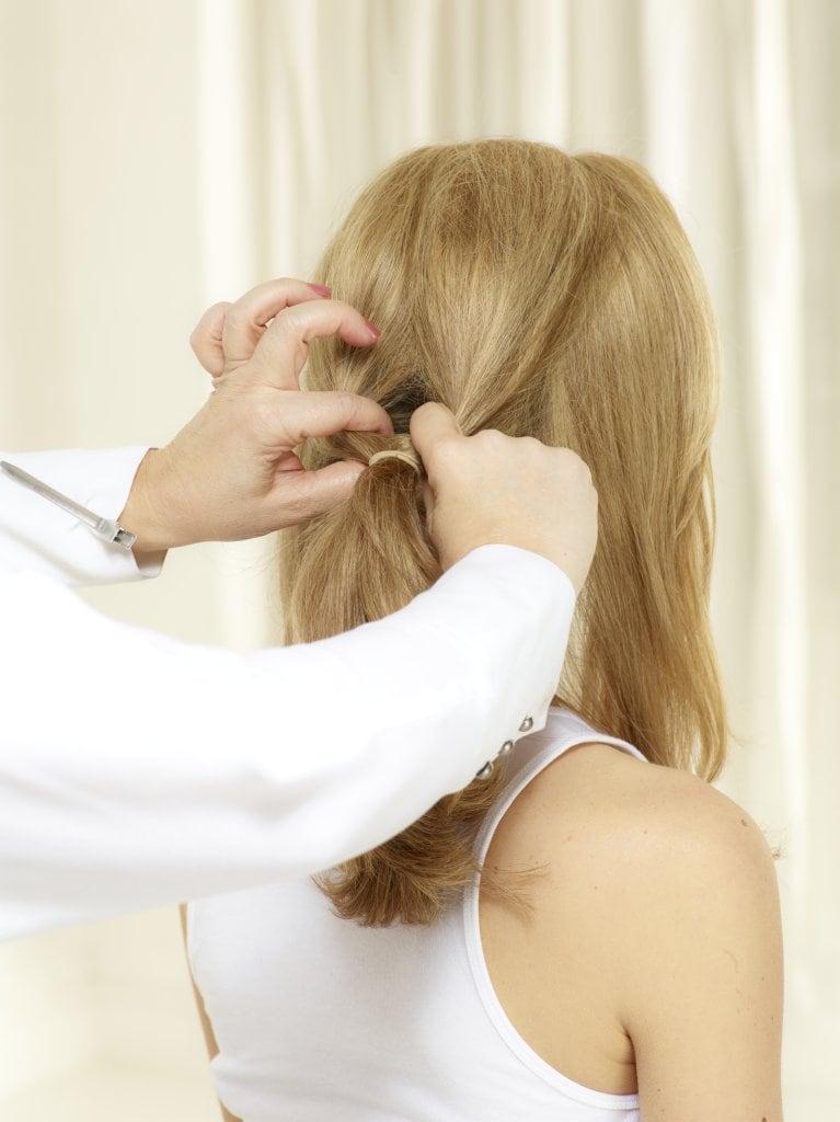 Oberhalb des Haarbandes ein Loch formen, Haare unterhalb des Bandes in zwei Teile teilen und durch das Loch ziehen