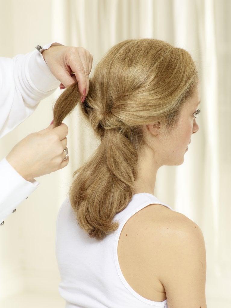 Seitliche Haarsträhnen ebenfalls durch das Loch ziehen, Haarspitzen am besten mit den Fingern lockern und Look mit Styling Spray fixieren.