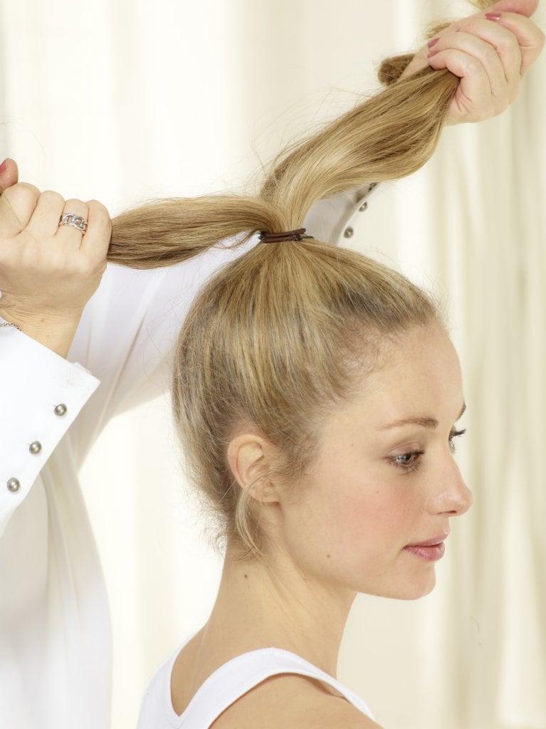 Haar mit nach unten gebeugten Kopf bürsten, dann zu einem hohen Pferdeschwanz zusammenbinden. Haar in zwei Teile trennen.