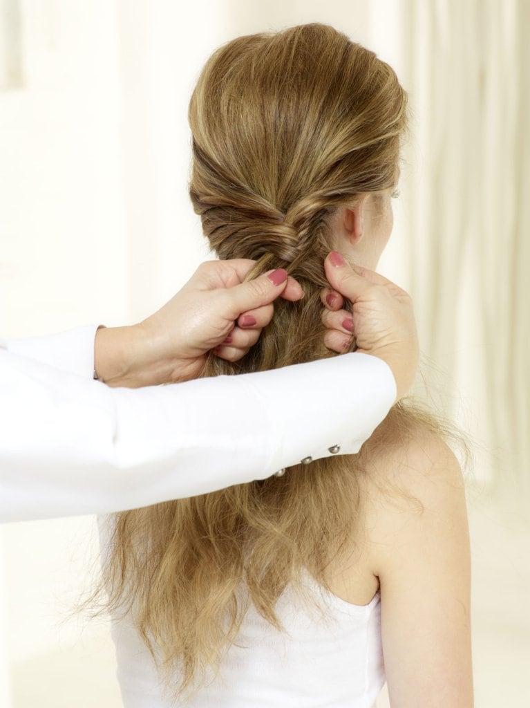 Von jetzt an immer eine schmale Strähne von aussen nach innen ziehen und zur gegenüberliegenden Strähne hinzugeben. © Beiersdorf