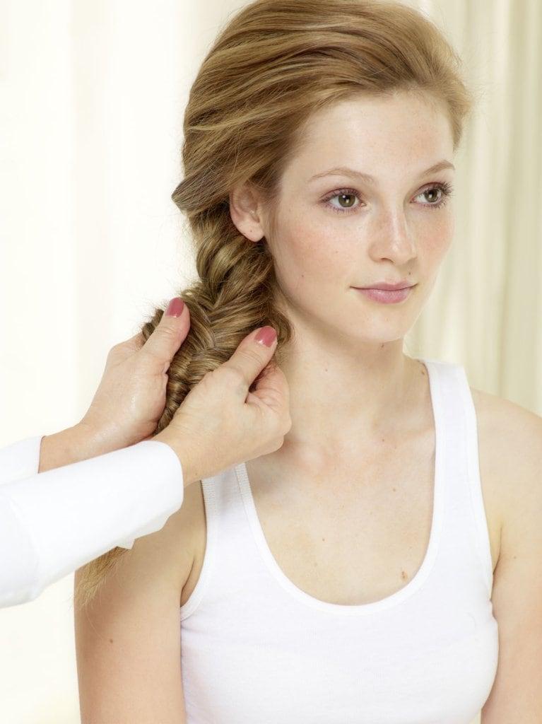Zopfende mit einem Haarband fixieren. Flechtwerk auseinanderziehen, damit der Zopf breiter und voller aussieht. Look mit Styling Spray fixieren. © Beiersdorf