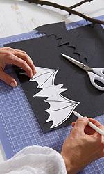 Aus dem festen Papier eine Schablone nach der Vorlage anfertigen. Die Fledermausvorlage auf die schwarze Pappe übertragen und ausschneiden.; Bildquelle: tesa