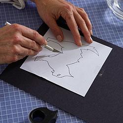 Die Katzenvorlage mit tesafilm® Eco & Clear auf die Pappe kleben und mit dem Bastelskalpell ausschneiden.; Bildquelle: tesa