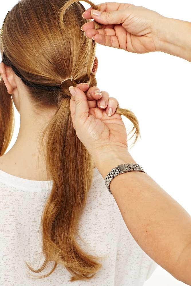 Die Haare zu einem tiefen Pferderschwanz zusammenbinden. Ein paar lange Strähnen vom unteren Teil des Pferdeschwanzes abteilen, nach oben bringen und ein paar Mal um sich selbst wickeln und mit Haarnadeln fixieren.