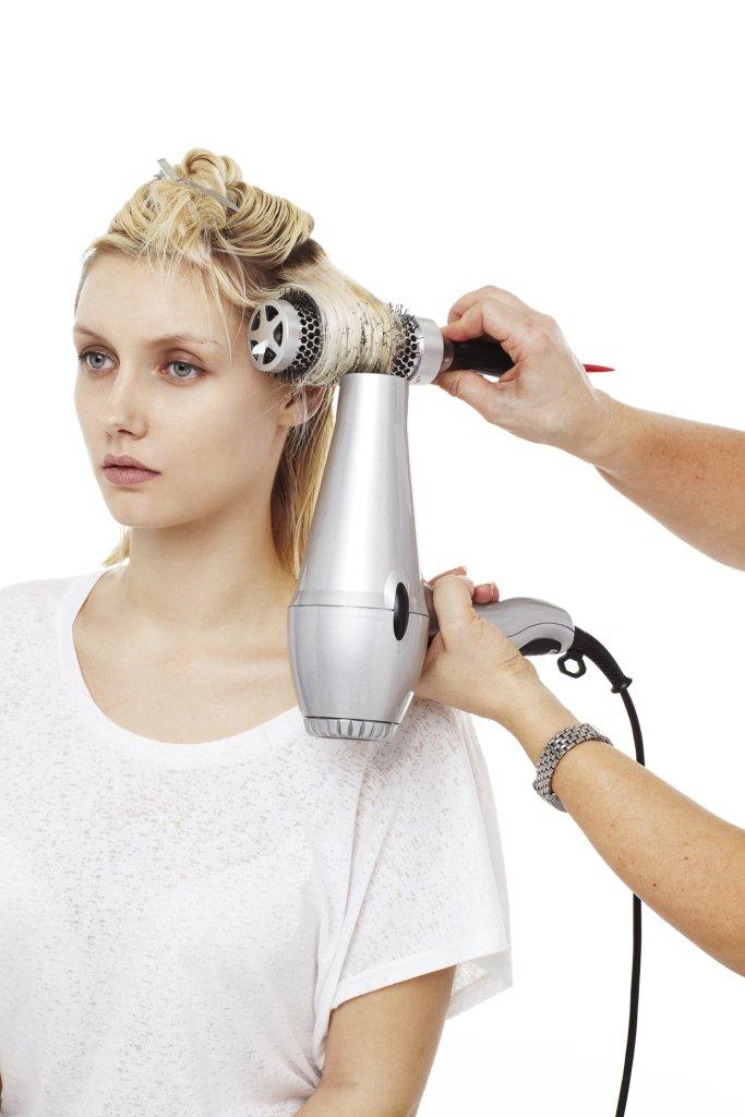 Die oberen Haare abteilen und erst die unteren Haare Strähne für Strähne über eine mittelgroße Rundbürste trocken föhnen.