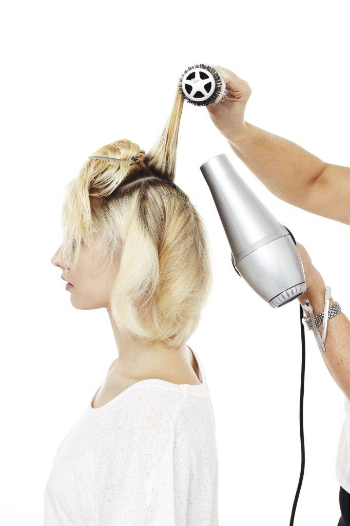 Das abgeteilte obere Haar auf dieselbe Weise trocken föhnen. Hinten beginnen für mehr Volumen.