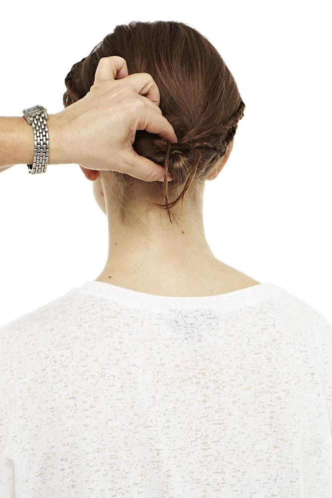 Haare zu einem Knoten schlingen und Zöpfe darin fixieren.